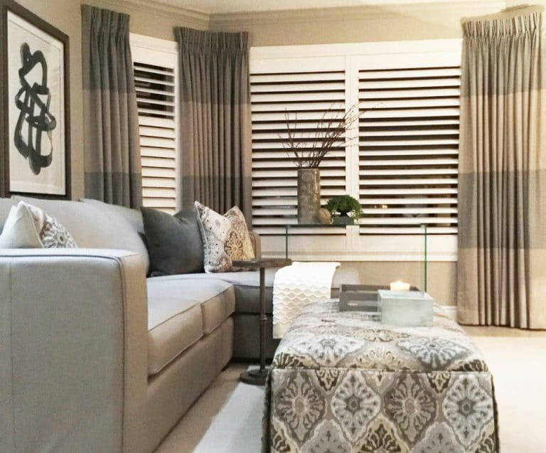 Family room featuring grey linen sectional, upholstered ottoman, linen drapes and white California shutters
