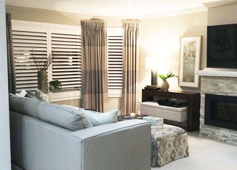 Family room with upholstered ottoman, slate fireplace, linen drapes and California shutters