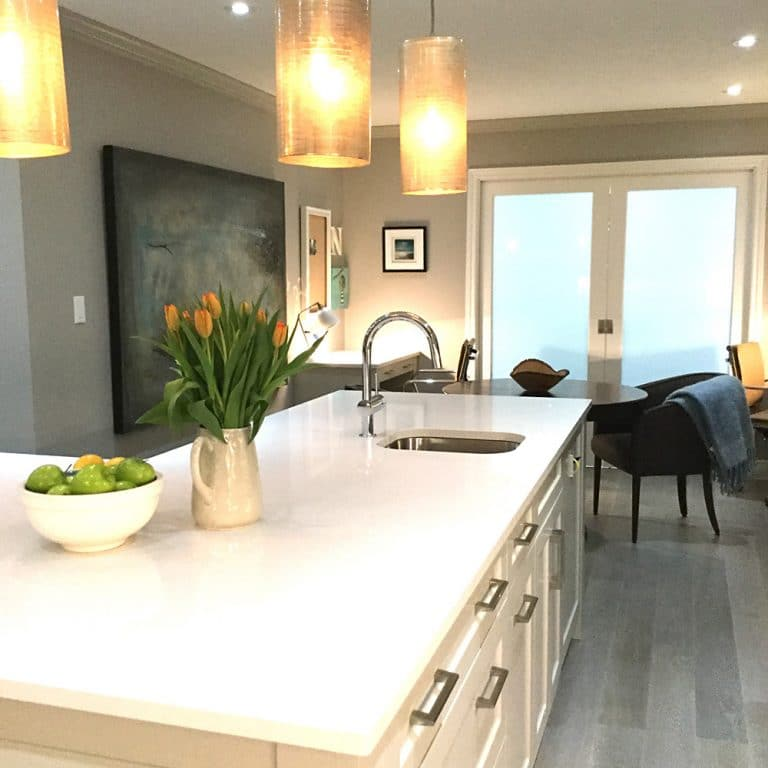 Kitchen with white quartz countertop, stainless steel sink and hanging yellow glass lighting