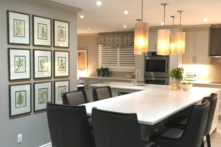 Kitchen with white quartz countertop and seating for 6 with hanging glass lights