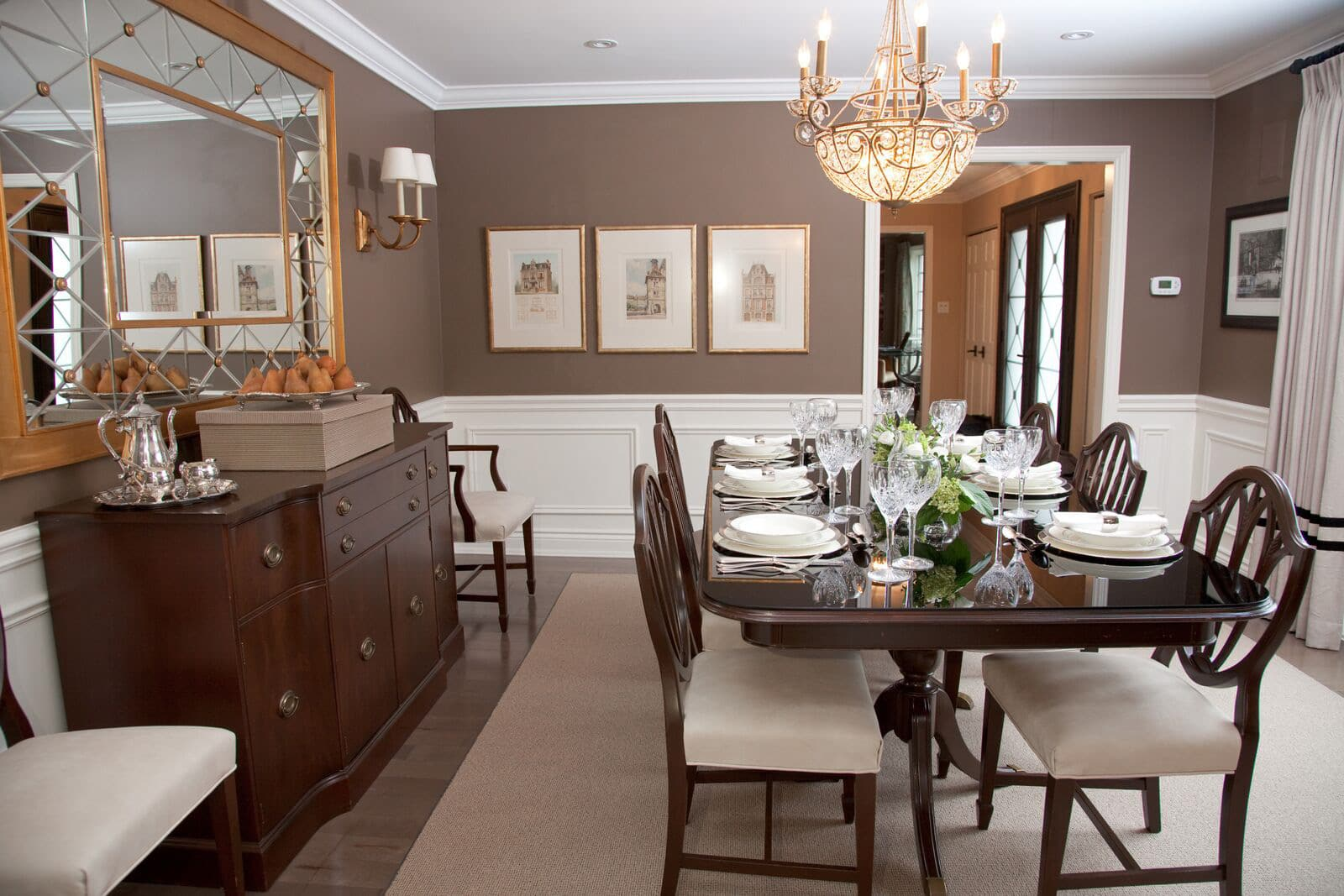 Dining room with formally set table, china cabinet, silver tea service, crystal chandelier, leather upholstered chairs and gold antiqued mirror