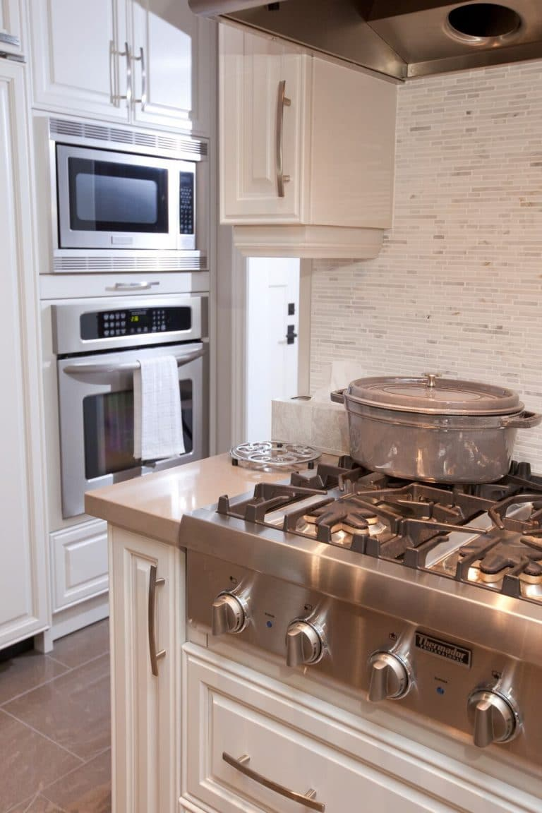 Kitchen with white cabinets with light grey backsplash, featuring thermador gas-top stove, grey staub cocotte, wall oven, wall microwave