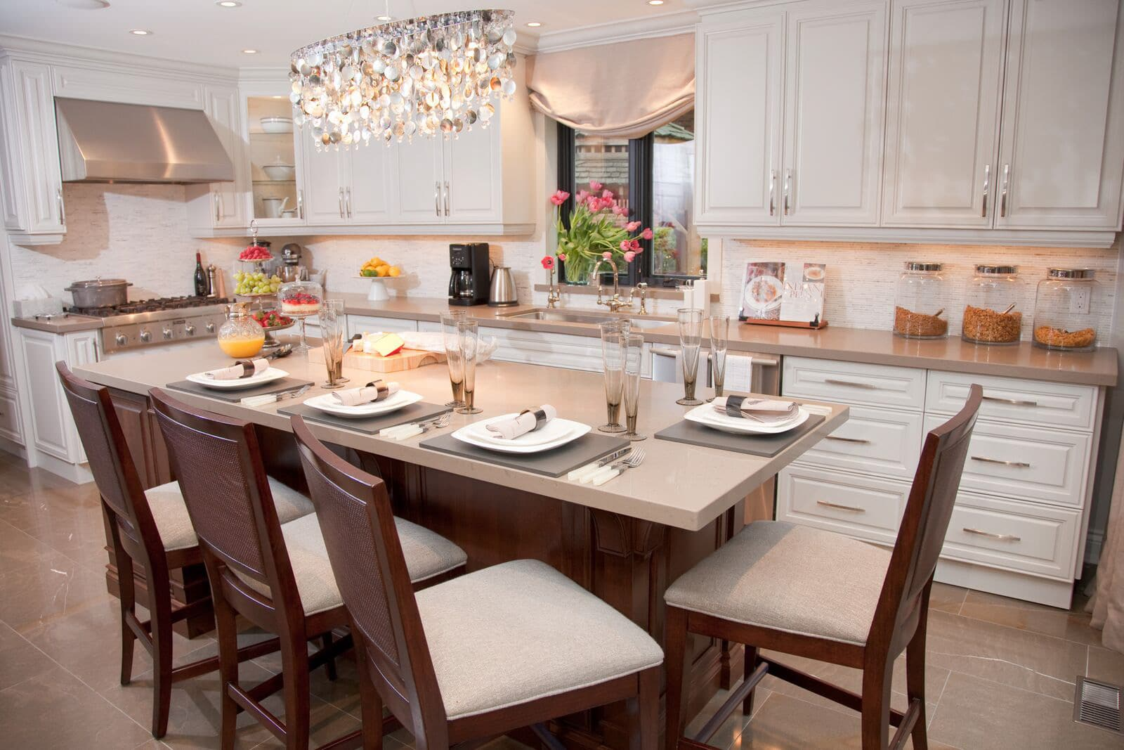 Kitchen with set table featuring white main cabinets, brown cherry wood island, olive quartz countertop, olive marble floor and opsalescent chandelier