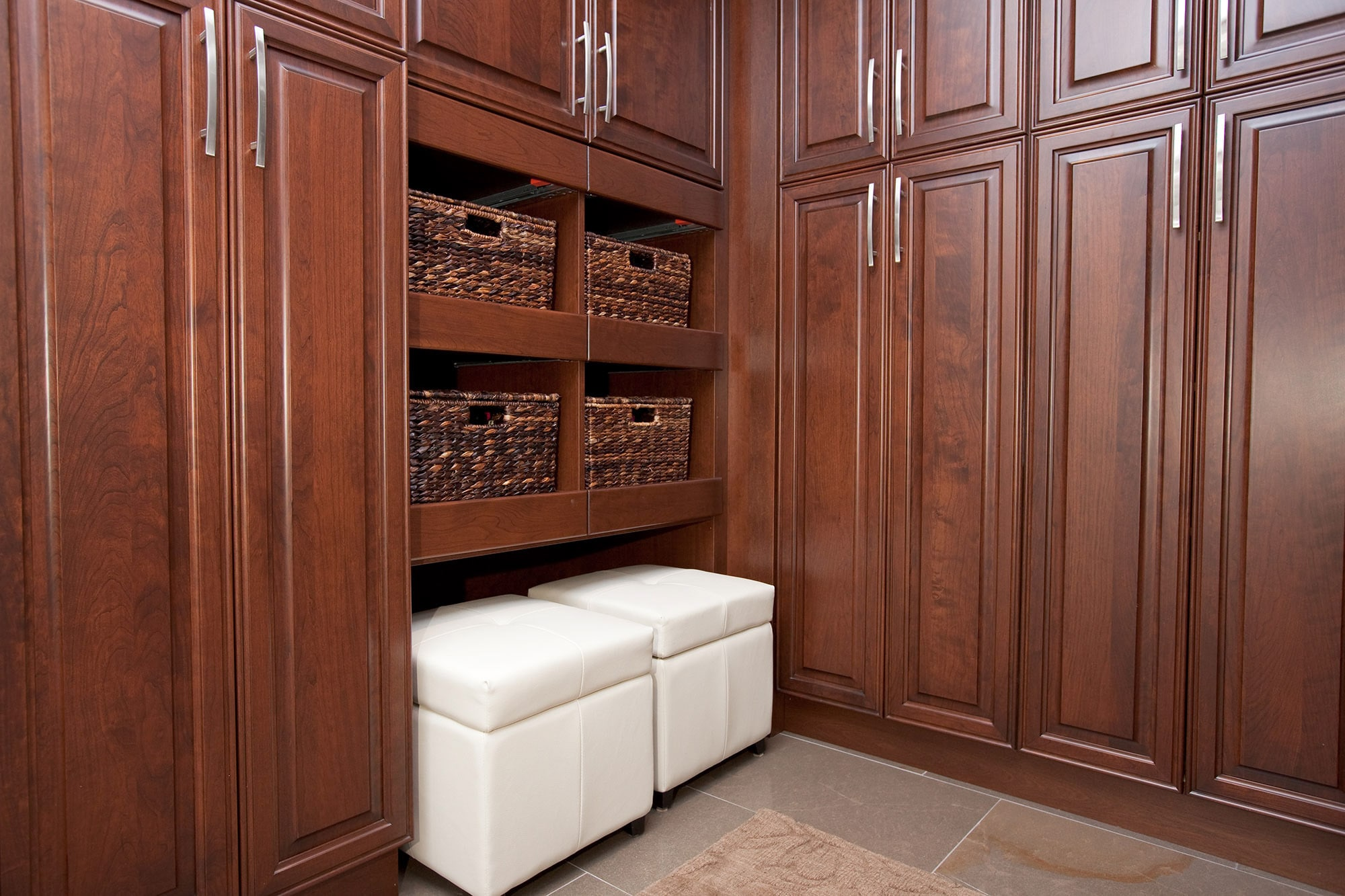 Mudroom featuring build-in cherry storage cabinets, wicker storage baskets and white leather box seating