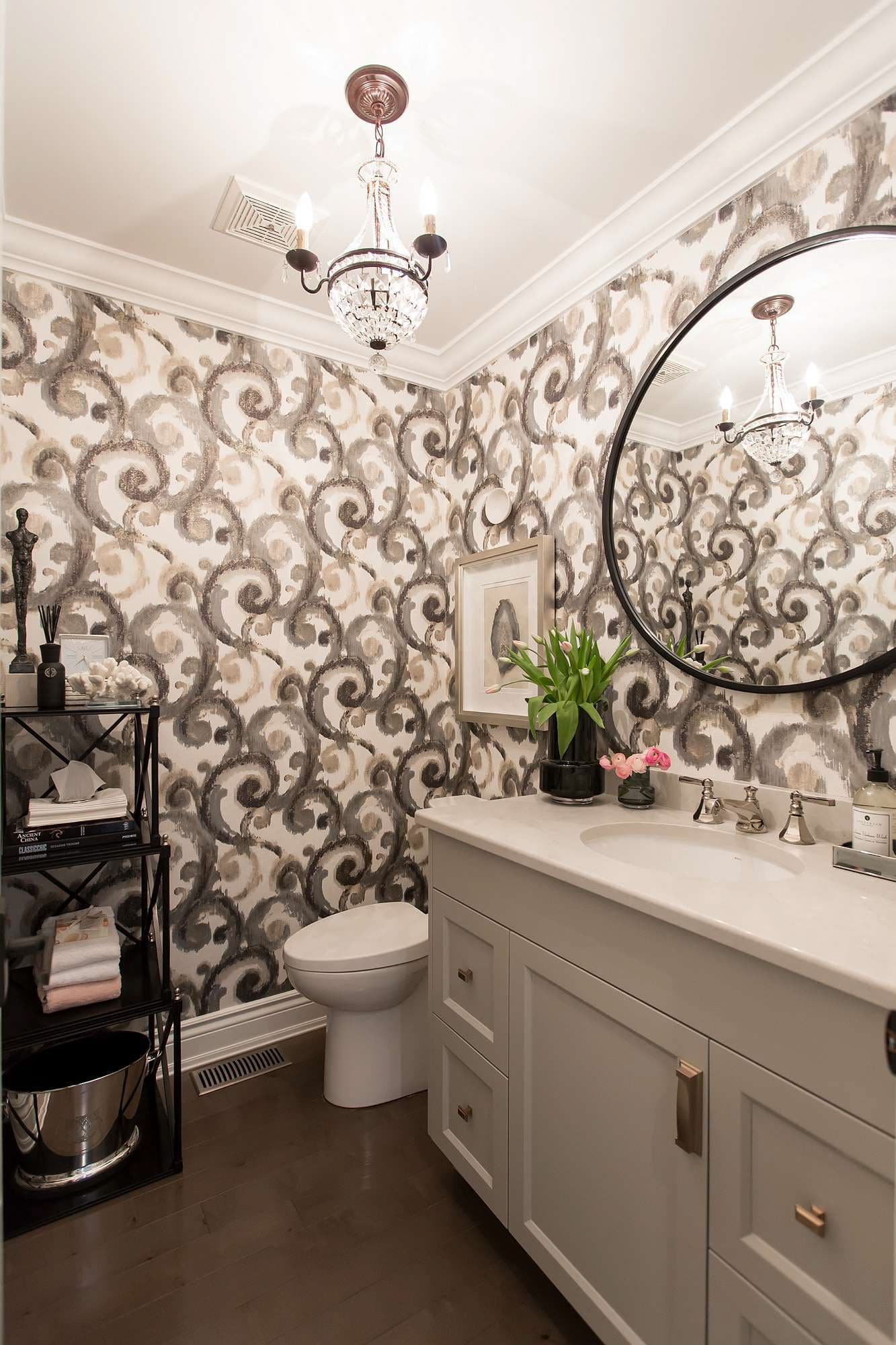 Powder room with scroll wallpaper in black, olive, cream and gold, cream cabinets with cream quartz countertop