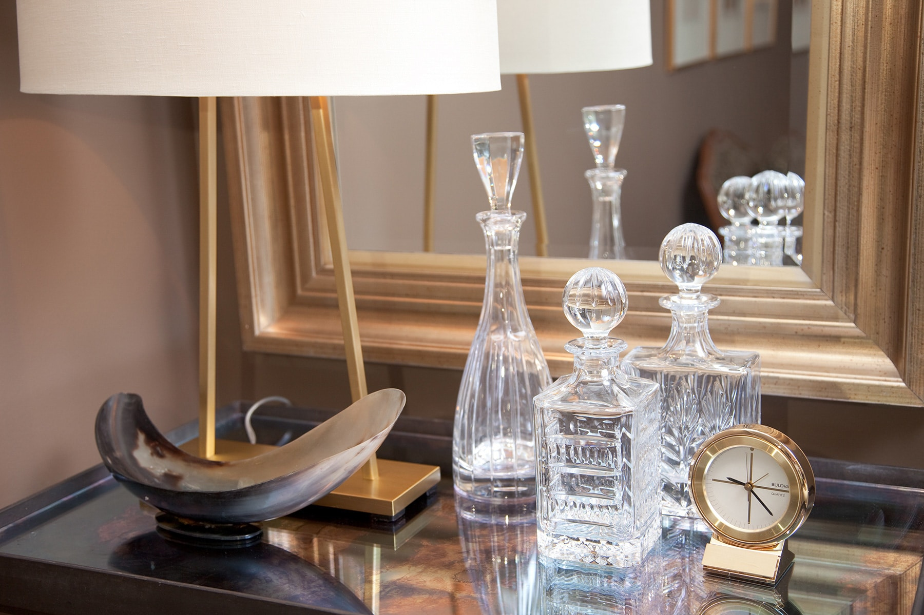 Tabletop with crystal decanters, gold plated desk lamp, horn tray, gold plated clock and gold antiqued mirror