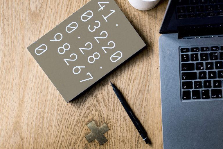Budgeting process represented by digits on a notebook, pencil, notebook computer and coffee mug