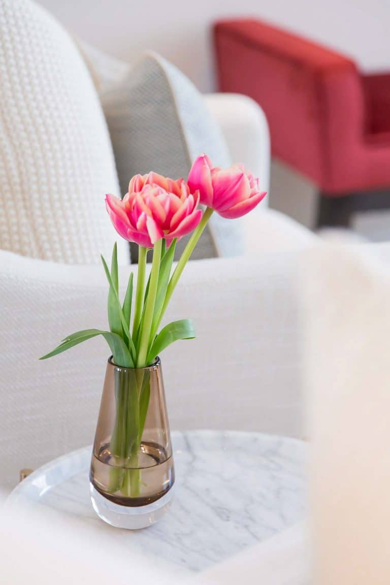 Cream Armchair with marble side table and pink tulips in glass vase