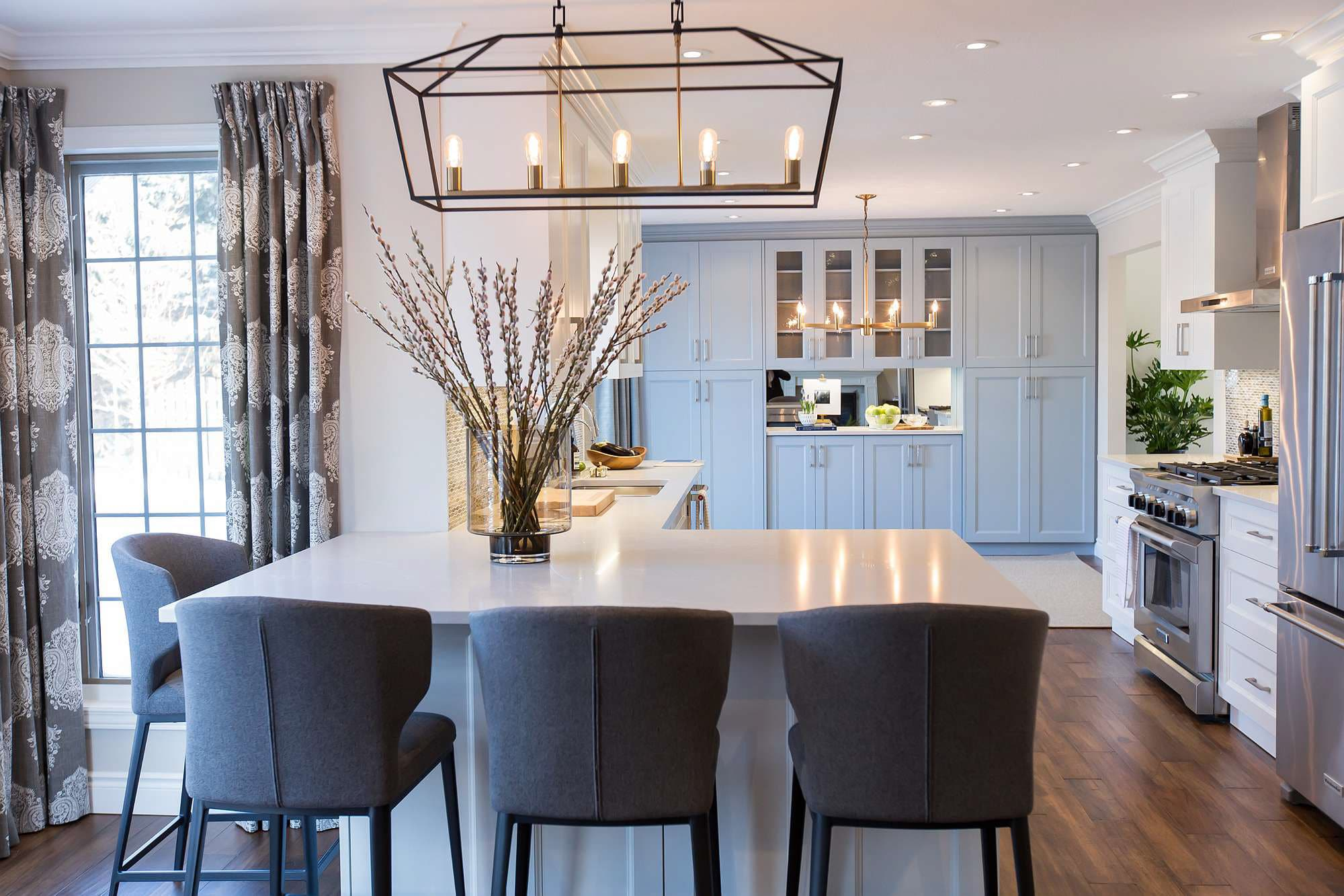 Kitchen Island with white cabinets and grey quartz countertop with grey wool upholstered stool, Hanging wrought iron light and antique hardwood floor