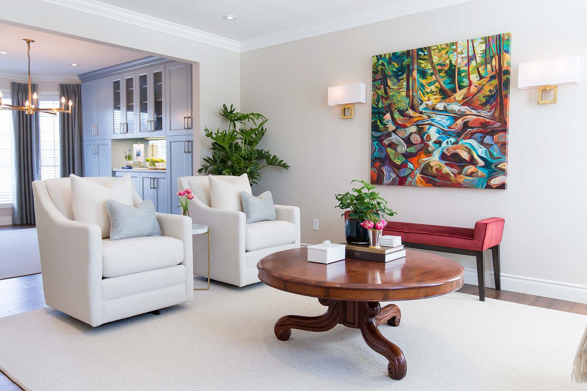 Living Room featuring wood coffee table, red velvet bench, white linen armchairs, colorful outdoor art and dining room with blue built-in cabinets