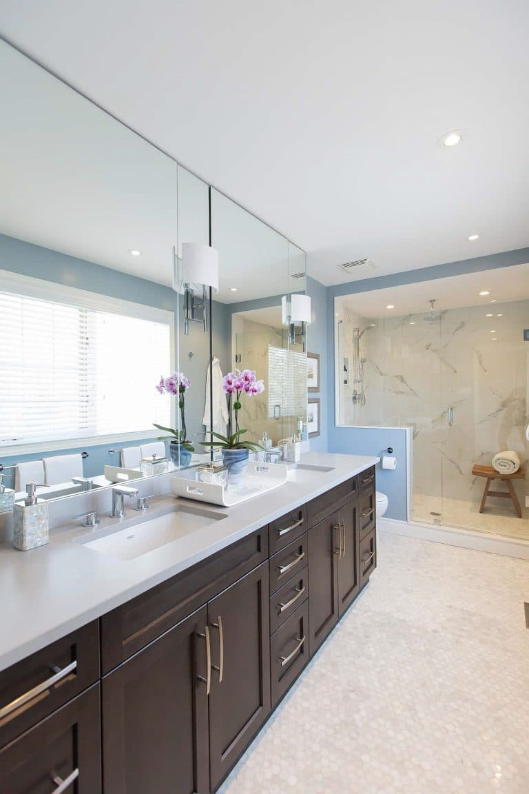 Bathroom with blue walls featuring brown wood cabinets, quartz countertop, marble shower with wood seat and marble hexagon tile floor