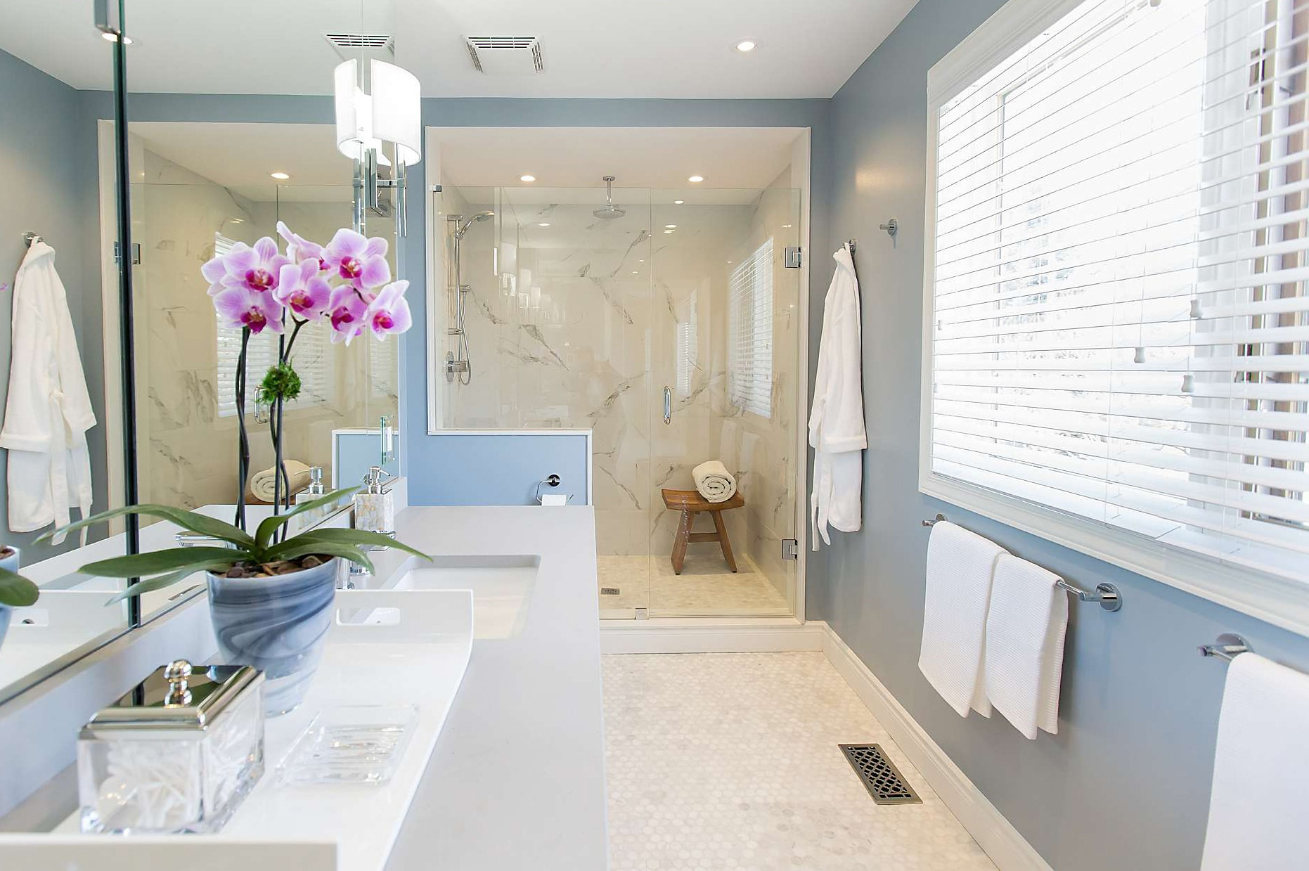 Master bathroom with blue walls featuring quartz countertop, marble shower, tile floor and glass planter with pink orchid