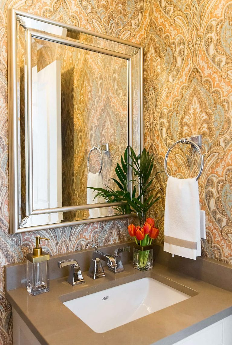 Powder room with grey quart countertop, paisley wallpaper, bevelled mirror and glass planter with orange tulips