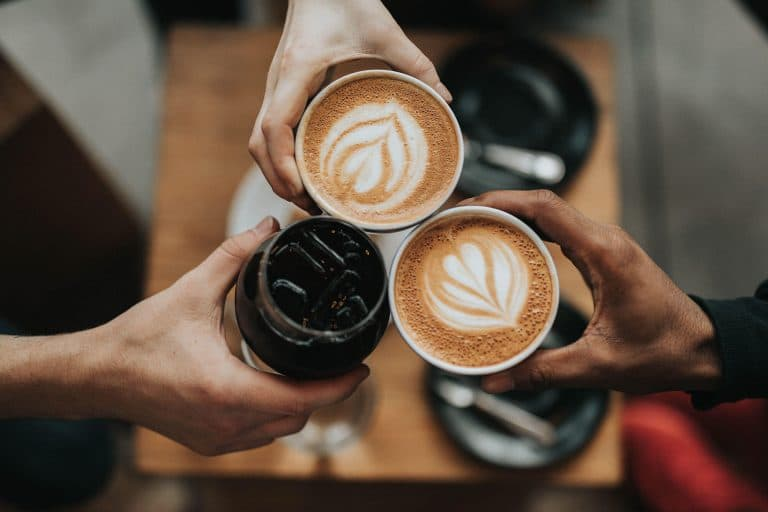 Close-up of three friends offering cheers with two coffee mugs and an iced tea