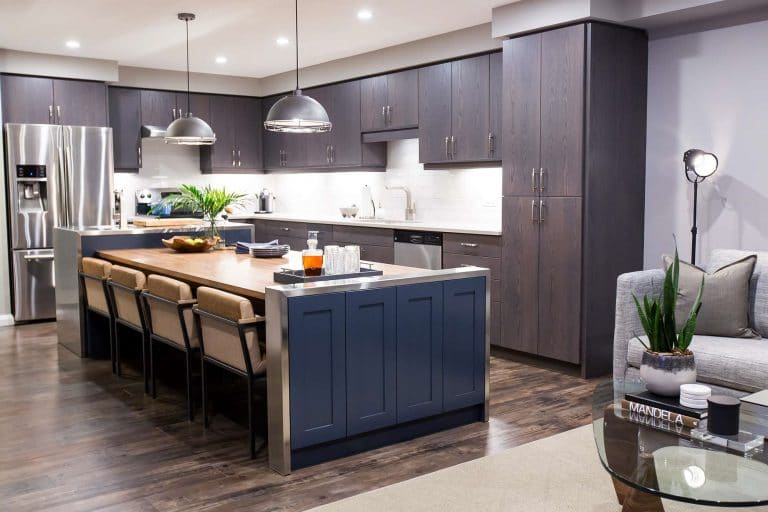 Hybrid kitchen island solid walnut dining room table bookended with navy blue cabinets shrouded with stainless steel waterfall tops