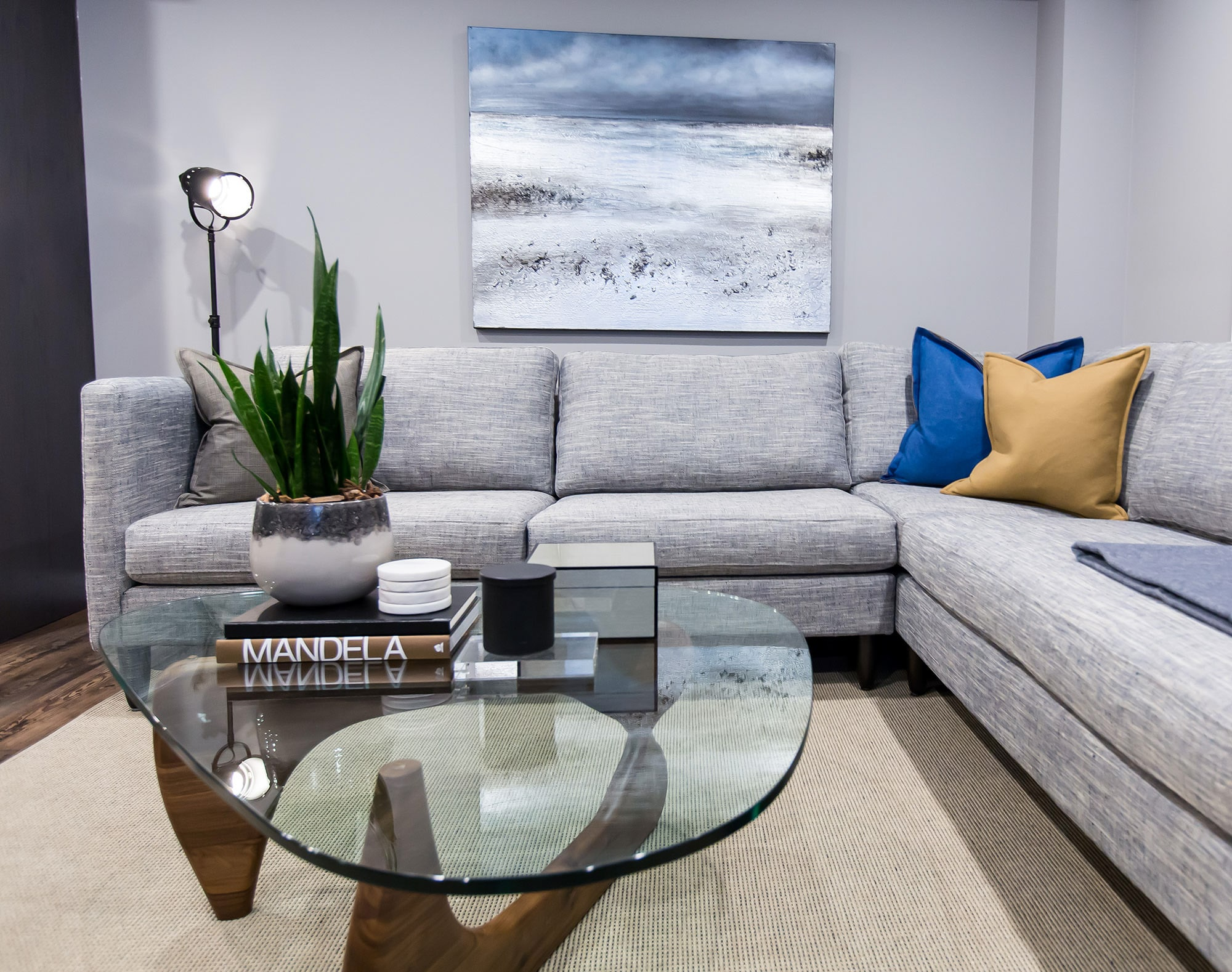 Living room featuring grey linen sectional sofa and architectural coffee table with glass top and wood base