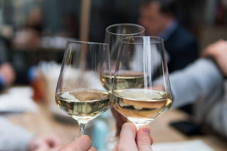 Close up of three friends clinking white wine glasses