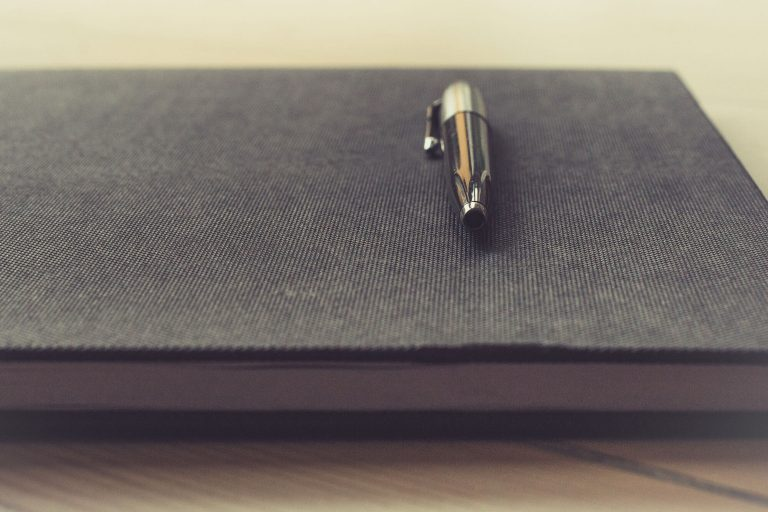 Black cloth covered notebook with pen resting on top