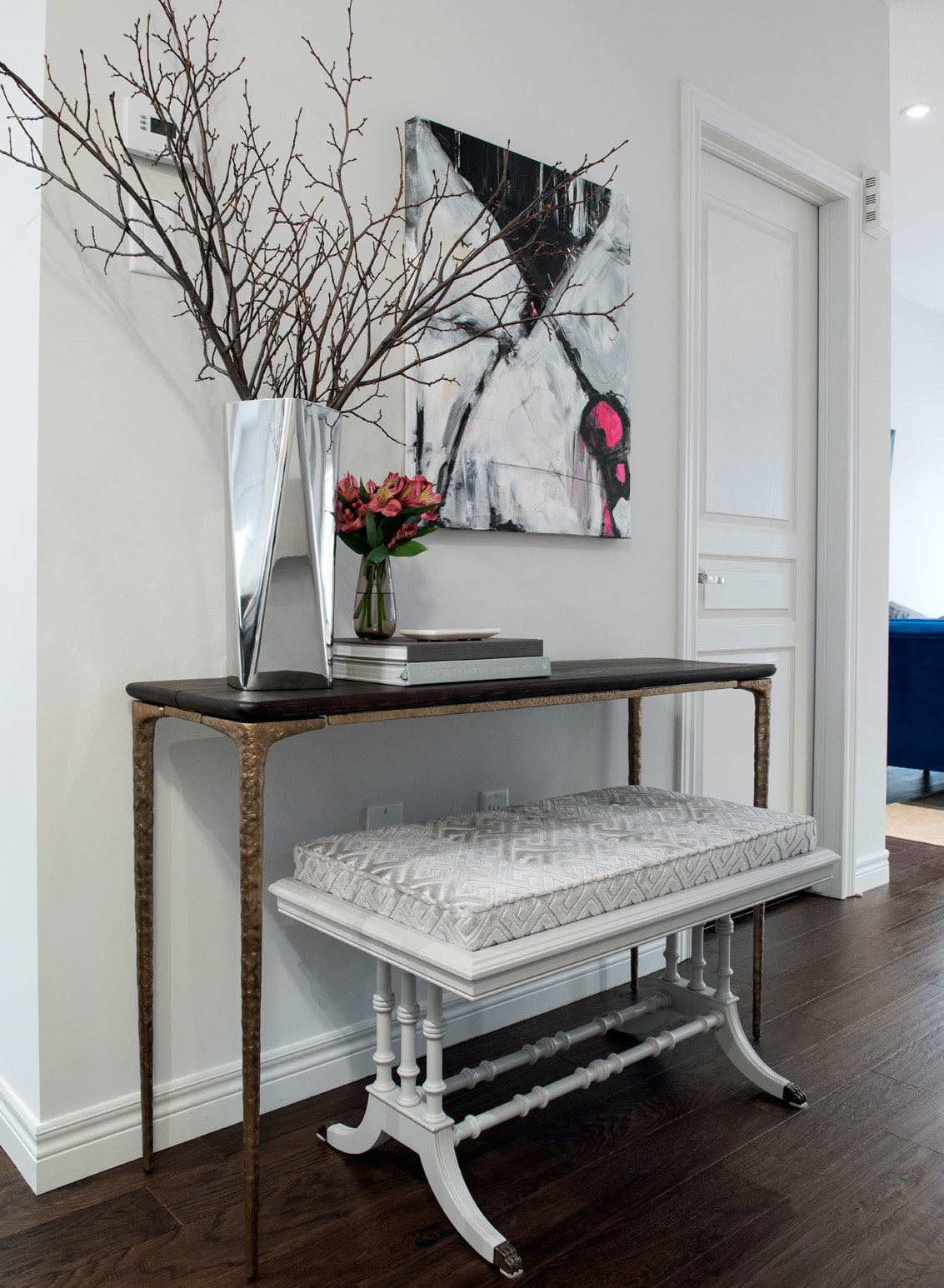 Antique console table featuring antique bench with grey velvet upholstery and mirrored silver planter and black, white and pink oil painting