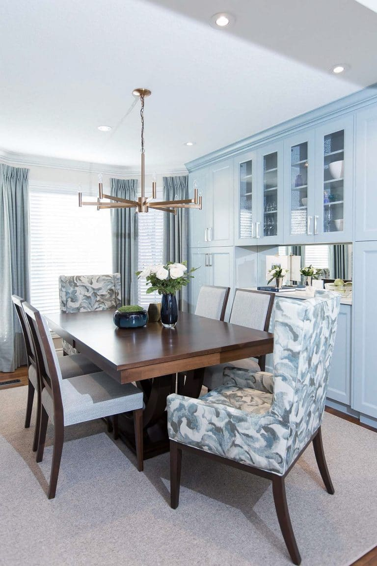 Dining room featuring brass hanging light, wood table, built-in cabinets, blinds and drapes