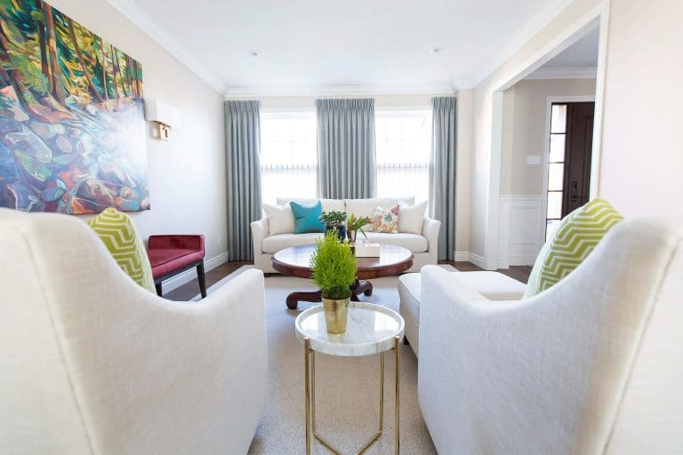Living room featuring off-white linen sofa and swivel armchairs with layers of cushions and drapes
