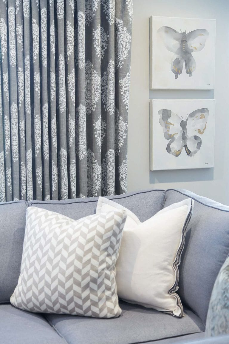 Sectional sofa close-up featuring cool-neutral pillows, drapes and artwork