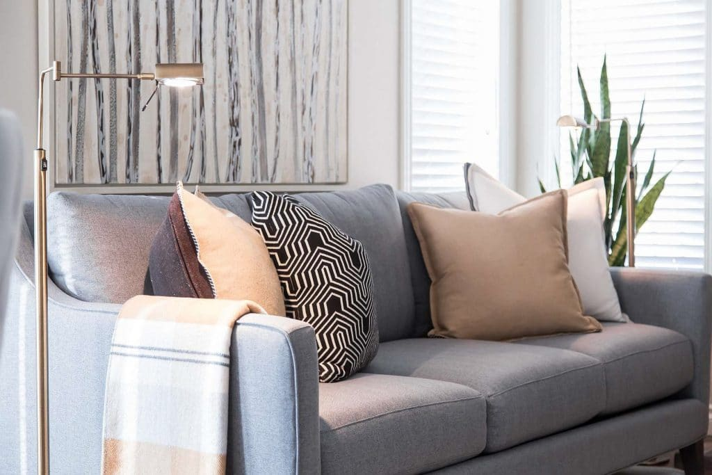 Grey linen sofa featuring warm neutral pillows and throw, floor standing reading light and poplar oil painting