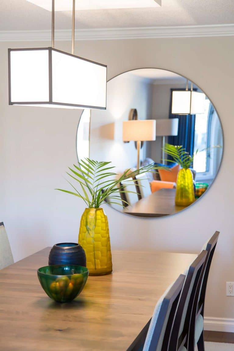 Dining room featuring solid wood table, green glass bowl, blue and yellow glass planters and large circular mirror.