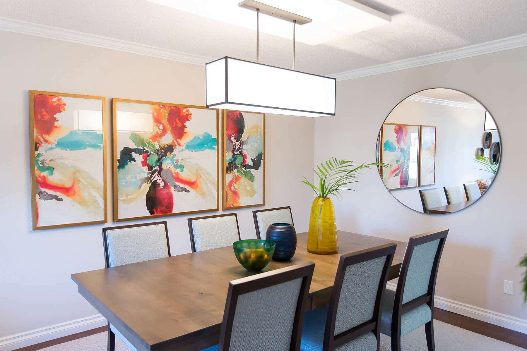 Dining room featuring solid wood table, three panel artwork, suspended over-table lighting and large circular mirror