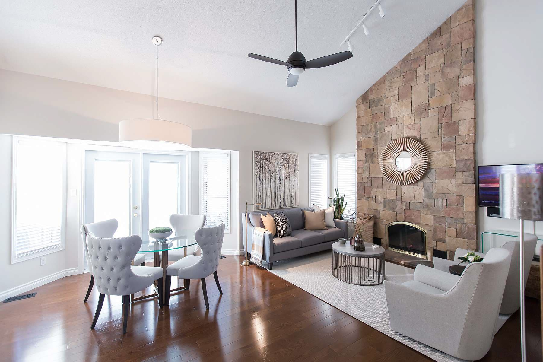 Family room featuring natural stone full wall hearth and multiple seating areas