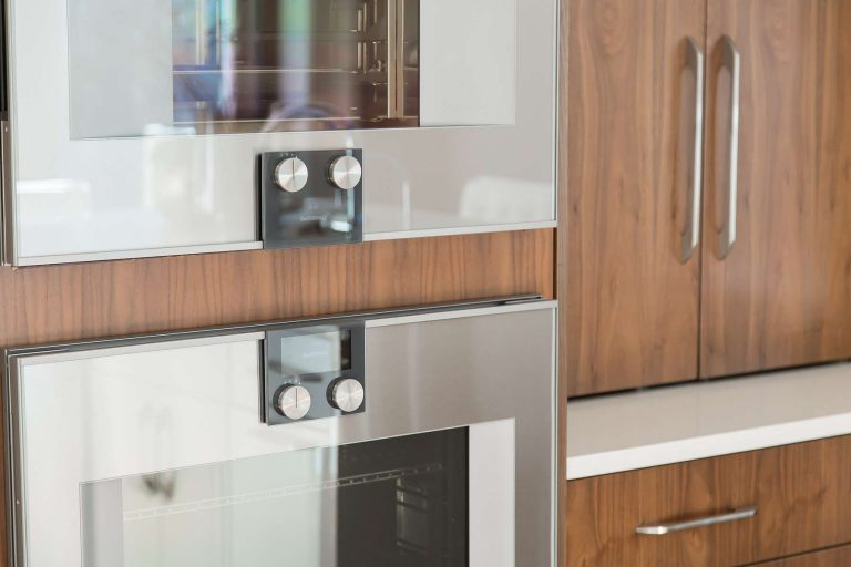Double wall ovens mounted in walnut cabinetry with large stainless steel door pulls in matte finish