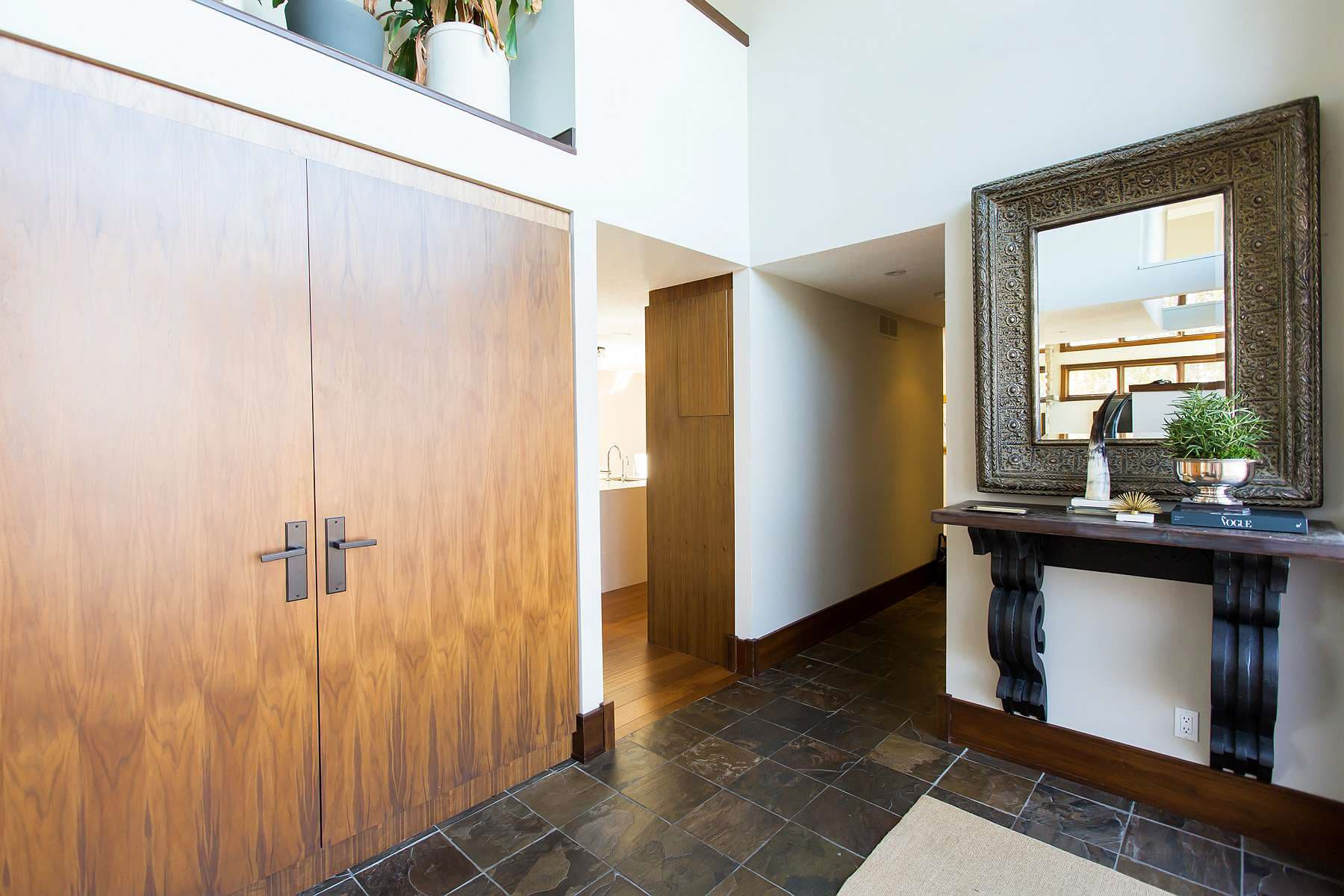 Foyer featuring large solid wood closet door, wall-mounted console table with antique mirror and slate flooring