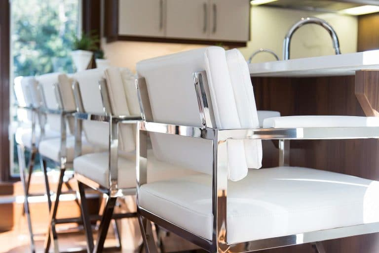 Kitchen island stools featuring white leather upholstery and chrome frame