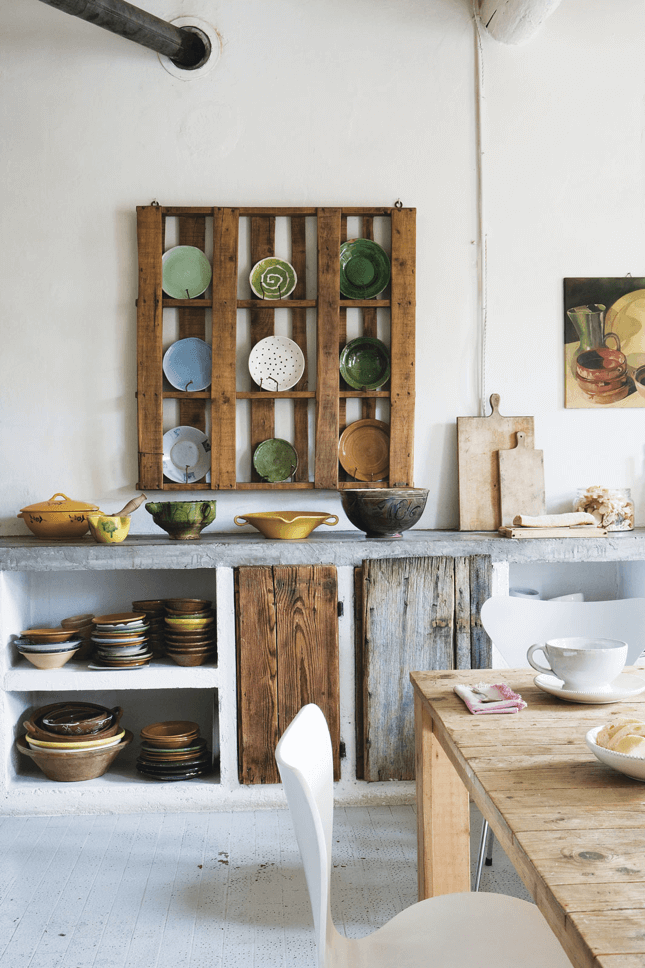 Deconstructed kitchen trend reclaimed wood pallet, rustic cabinet doors and vintage pottery