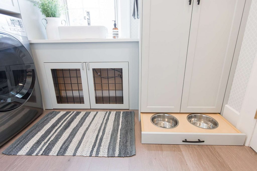 Laundry room featuring cabinet with pull out dog bowls and cabinet with built-in dog cage