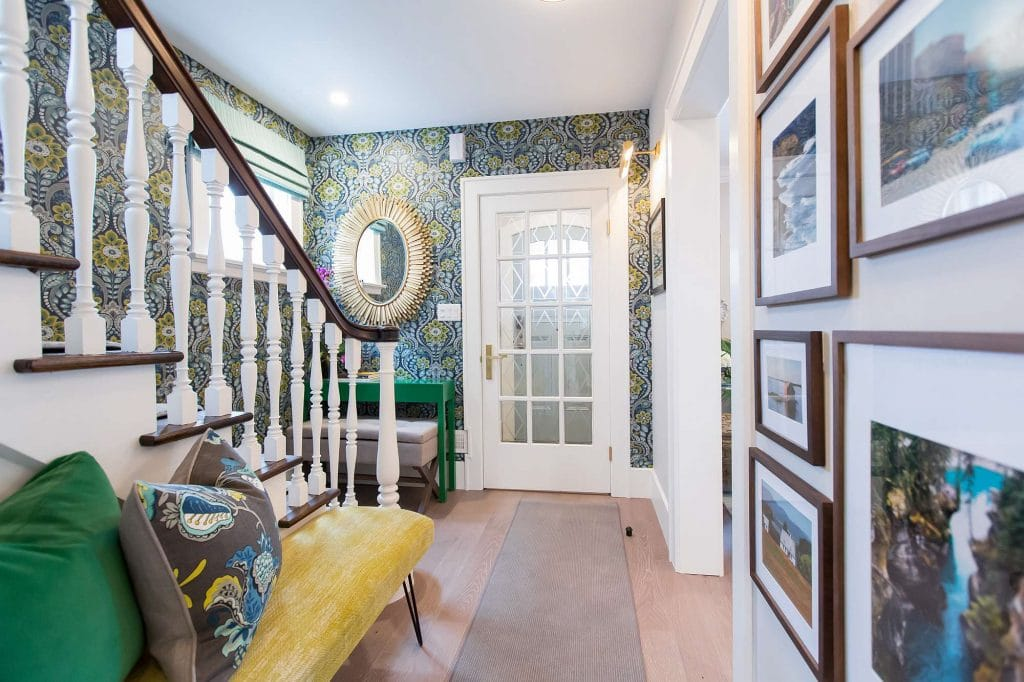 Foyer featuring white french door, hardwood floor with runner, gold leaf mirror on floral wallpaper and picture frame gallery and yellow velvet bench seating
