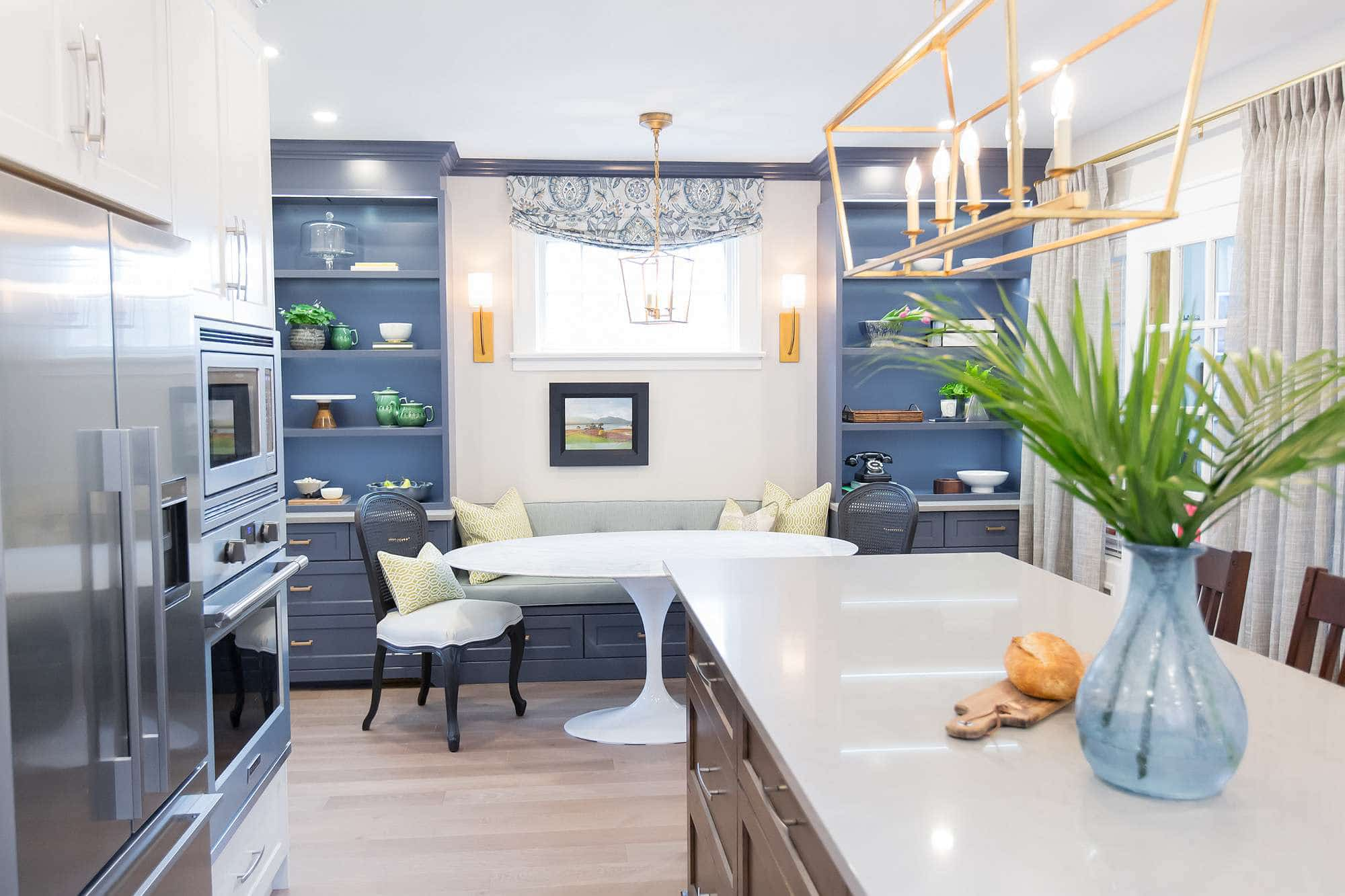 Kitchen featuring white main cabinets with double stainless steel wall oven and fridge, and stained wood island with off white quartz counter top and dining room featuring white marble top oval table, banquette seating and cabinet with upper open shelving