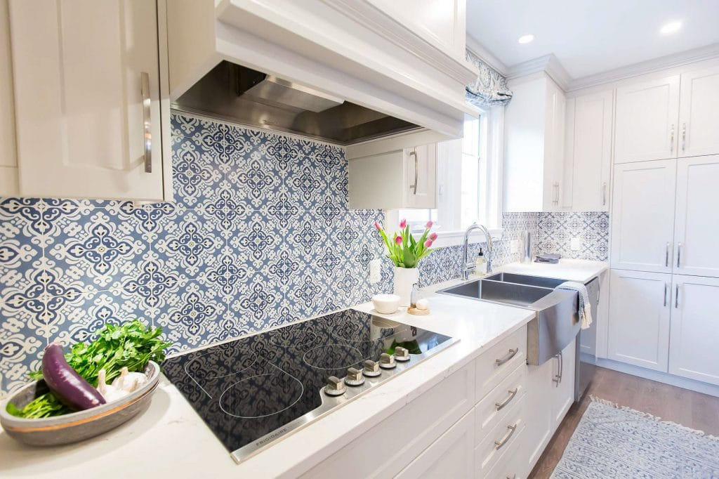 Kitchen featuring white cabinets inductive heating cooktop and stainless farmers sink and blue and white floral geometric backsplash with blue and white runner on hardwood floor