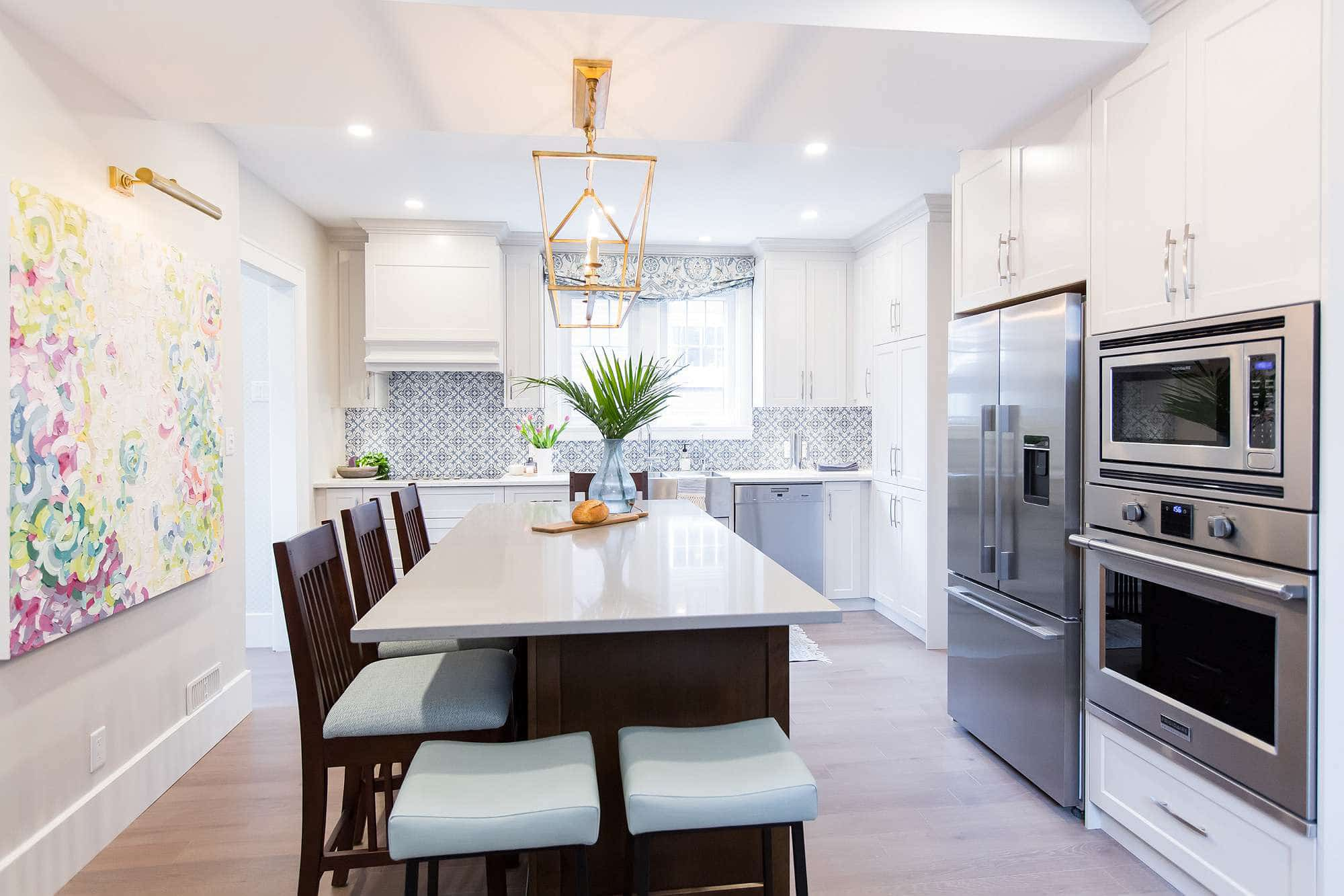 Kitchen featuring white main cabinets and stained wood island with seating for five with overhead hanging gold leaf lighting and built in wall oven and microwave and stainless steel double door fridge with drawer freezer