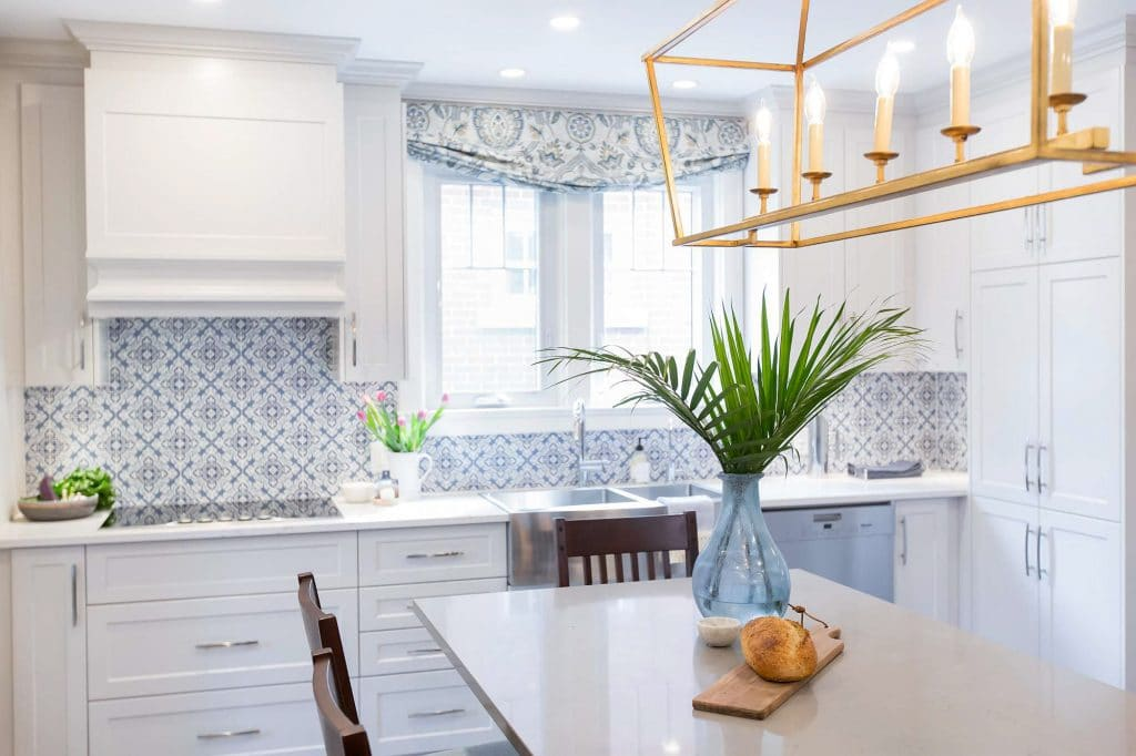 Kitchen featuring white cabinets and geometric floral blue and white backsplash and window valence and kitchen island white grey green quartz countertop with overhead hanging gold leaf lighting