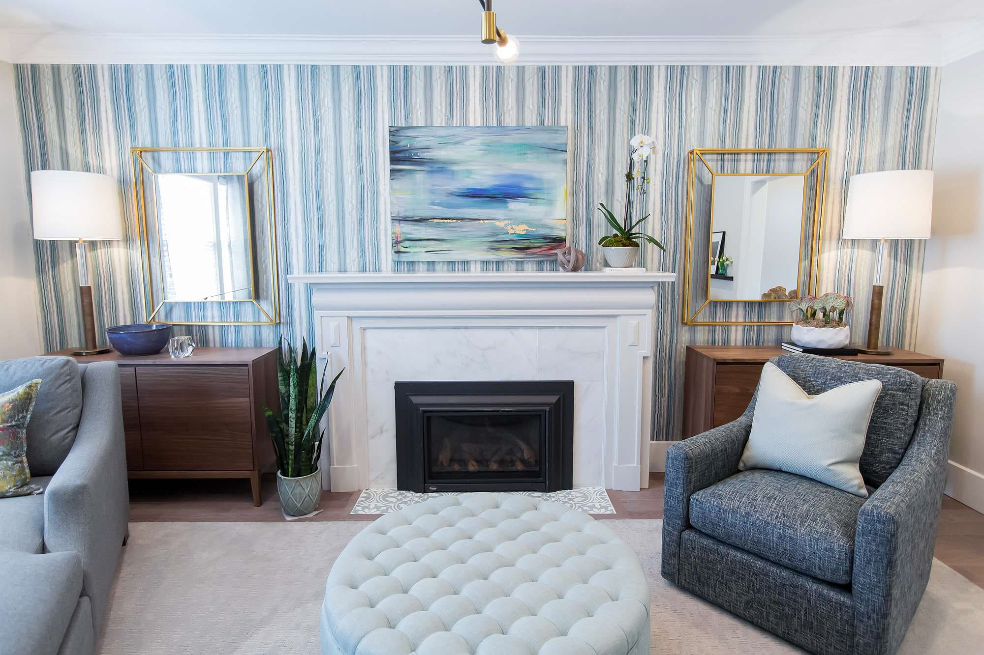 Living room featuring gas fireplace with marble surround and tile apron with blue and gold abstract art bookended with wood cabinets with gold leaf mirrors
