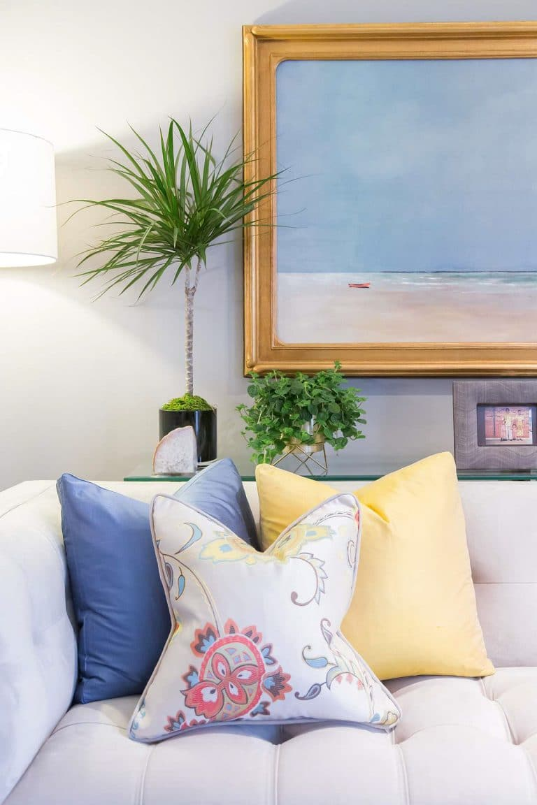 Blue and Yellow Pillows on Tufted Button Sofa with Beach and Sun Oil Painting
