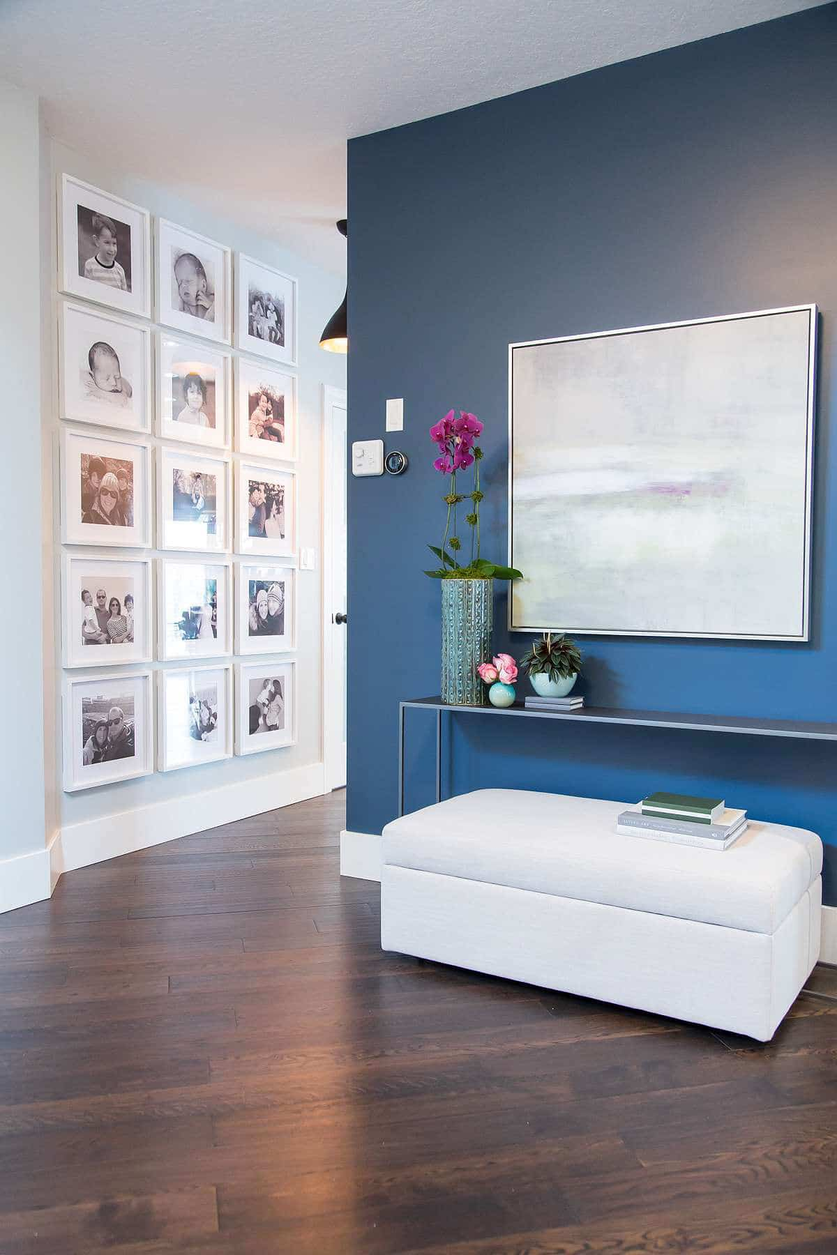 Blue Accent Wall with oil painting, white bench seating with storage, and chrome console table and white photo wall