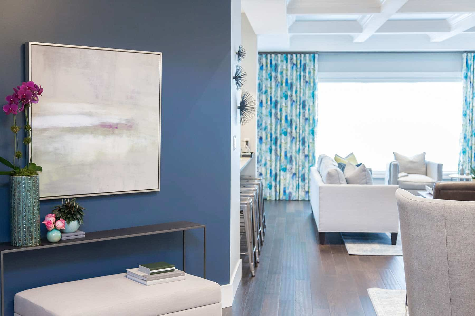 Blue accent wall with oil payinting with view to family room featuring Amaya vintage linen drapes with blue floral pattern