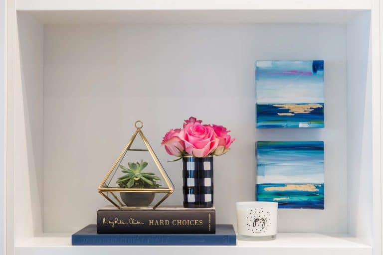 Cabinet niche with books, brass-framed vase, cermatic blue, white and gold rimmed vase with pink roses, joy glass candle and oil paintings of ocean in blue, green and gold