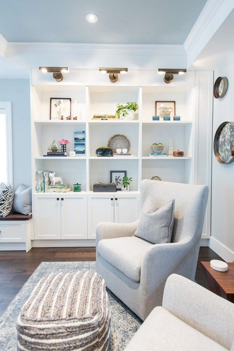 Family Room with white built-In wall unit with rubbed oil bronze picture light, open shelves, bottom doors and curved back armchairs in beige upholstery