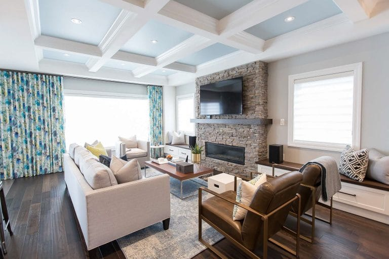 Family room with hardwood floor, with hand scraped oak, stacked stone fireplace, light blue upholstered sofa, ivory blue vintage rug, brown leather open brass frame armchair, large scale amaya vintage linen ripple fold drapes