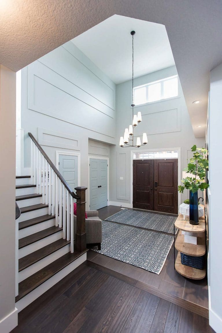 Front entrance with solid wood doors, hanging foyer lighting, solid wood console table with three shelves and panelled walls
