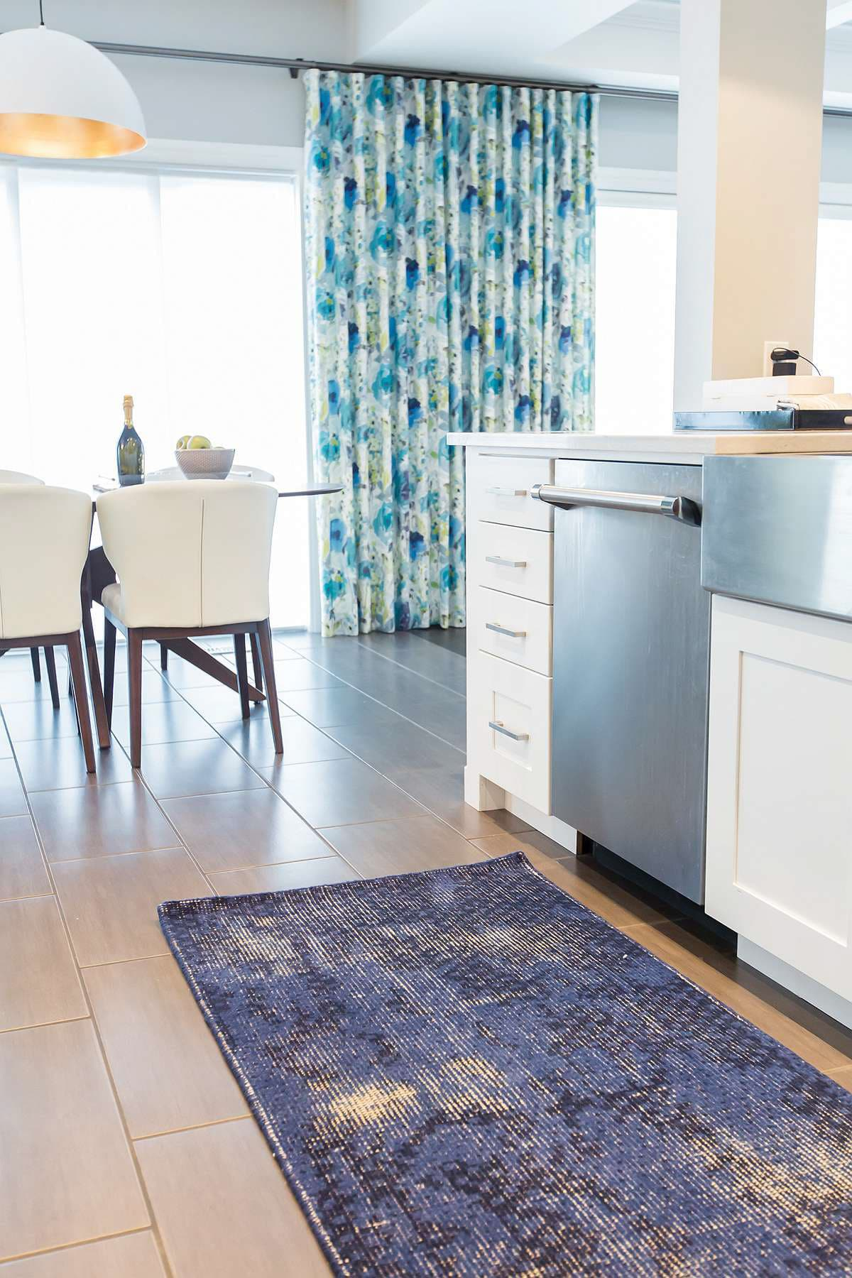 Kitchen with vintage blue and black woven rug with view of kitchen dinette and vintage Amaya drapes in blue, green and yellow floral pattern
