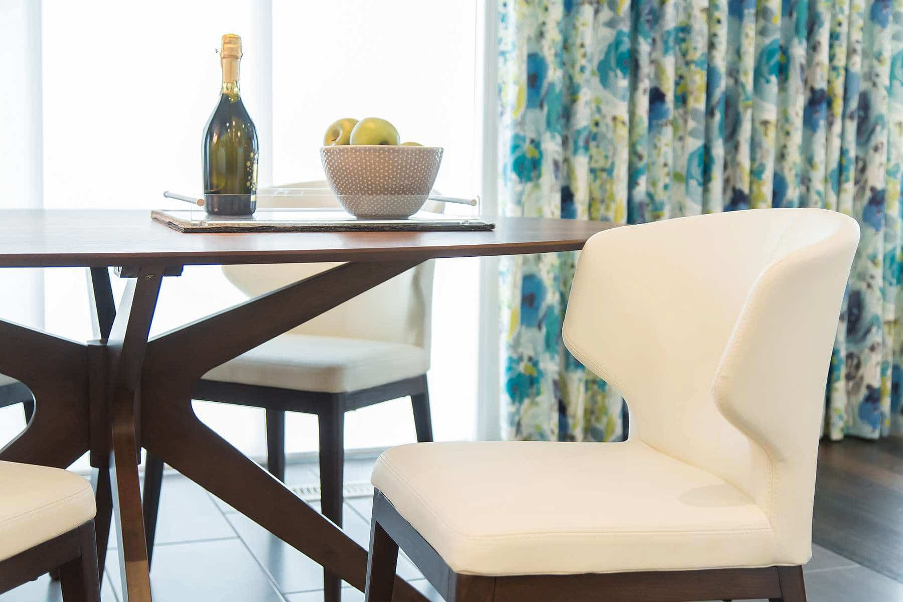 Kitchen dinette with curved white leather dining chairs and Vintage Amaya Linen drapes with blue, green and yellow floral pattern